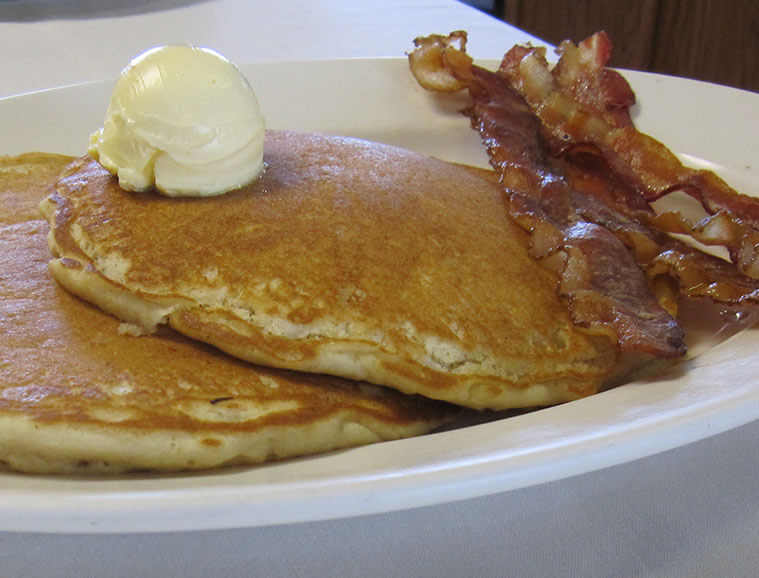 Plate of fresh buttermilk pancakes and cripsy bacon